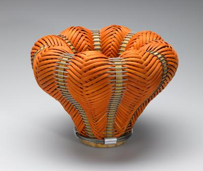 bowl-like form with thick sides and lip; orange reeds woven with natural reeds and steel twisted wires; two thick twisted wires at bottom with four cable connectors