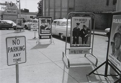 """four military recruiting signs, a No Parking sign and a sign reading """"White Waiting Room"""" on the sidewalk by a curving street"""