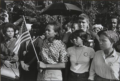 from left: woman with pocketbook, woman wearing pearls and gloves, young woman holding a small U.S. flag and wearing a flowered shirt, young woman in a striped shirt wearing a large coin pendant, tall young man in a jean jacket, young woman wearing a scarf