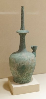 rounded body supporting a tall neck tapering to domed disk surrounded by a thin faceted sprinkling spout; set at one side with a tall waisted spout and attached lid. Koryo dynasty.