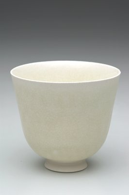 white pottery cup, unglazed foot with incised circle at underside of base, has own storage box