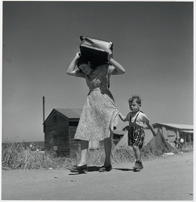 black and white photograph of woman carrying suitcase above her head with little boy beside her clutching her dress