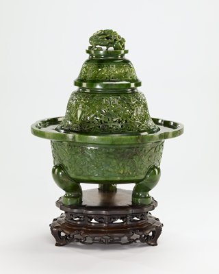 Censer, covered, of green jade in the form of a pagoda. The cover is in 3 sections carved with Buddhist symbol ; the finial a dragon surmonted by the praying mantis guarding the pearl of omnipotence. Body carved with all over foliate pattern, the rim with running Chinese fret. superb quality jade with begonia leaf marking. Brilliant emerald green in color.