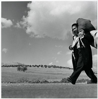 black and white photograph of man carrying a bag on his shoulder walking along a road