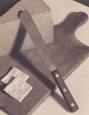 photo of cheese and crackers with knife on cutting board; mounted to board