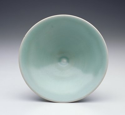 Shallow conical bowl with a very small foot; glazed light blue