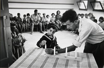 child dressed in sailor suit and 'U.S. Navy' hat lighting a candle which a man holds on top of a table; children and adults seated in background around edge of room; matted