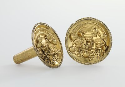 ear studs, pair, of hammered and engraved gold; the concave disks with beaded edges are decorated with an applied motif bearing four figures; above, a demi-god with elaborate aureloe headdress riding on a bar borne by three other figures; in one hand he holds a beaker-cup; in the other a bag adorned with loose bangles; two of the lower figures wear modified aureole headdresses and carry beakers; all are half-human, half-beast; the bar on which the demi-god rides is finished at the ends with demon heads; loose bangles are variously applied in the design; the tubes of the ear studs are decorated with engraved bands of cats and birds, and soldered to the backs of discs