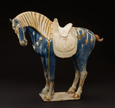 Horse with long mane and clipped tail. ca 725 A.D. Glazed pottery tomb figure, one of a pair, on a flat base. The decoration of the trappings is in the Sassanian style. Glaze predominantly a fine cobalt blue which has oxidized on the hind legs to an irridescent silvery-blue. Saddle and top saddle pad unglazed.