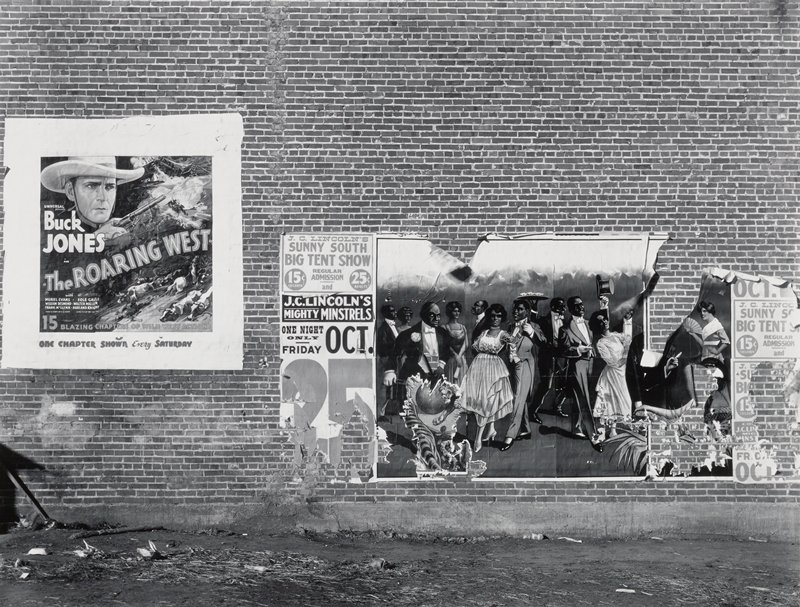 "torn poster with drawing of black entertainers on brick wall; ""The Roaring West"" serial poster at left"