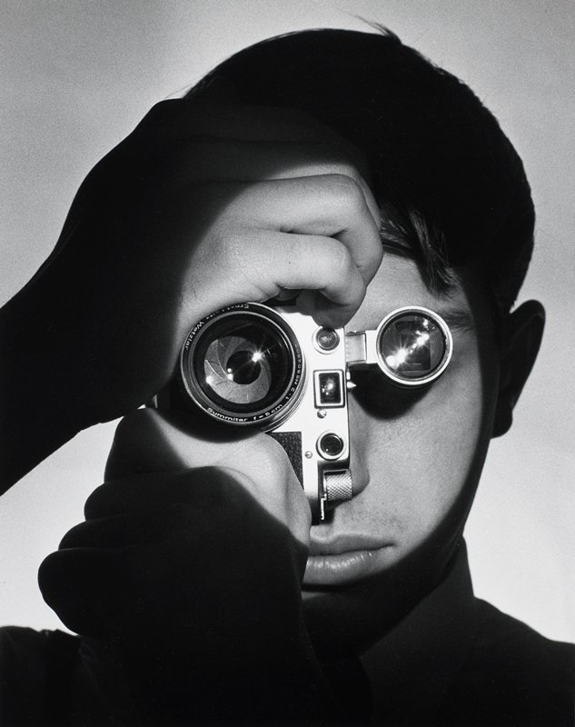 spotlight on face of figure holding a camera to eye - head and hands only in picture; lens of camera and flash appear in position of eyes