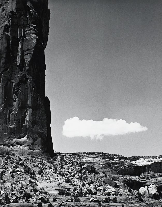 low, very white cloud in right center; large black cliff at left side; fallen and broken rocks in foreground