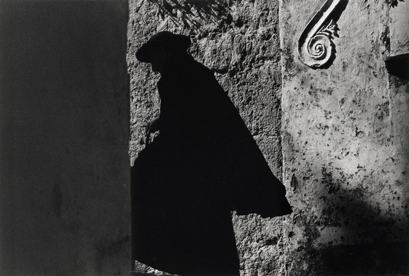 black figure, in shadow, wearing long garment, cape and cap; stone wall in background, with curving applied architectural element in upper right corner