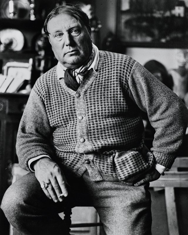 heavy-set man seated on a stool, holding a cigarette in his proper right hand and with his proper left hand on his hip; man wears cardigan sweater with neckerchief