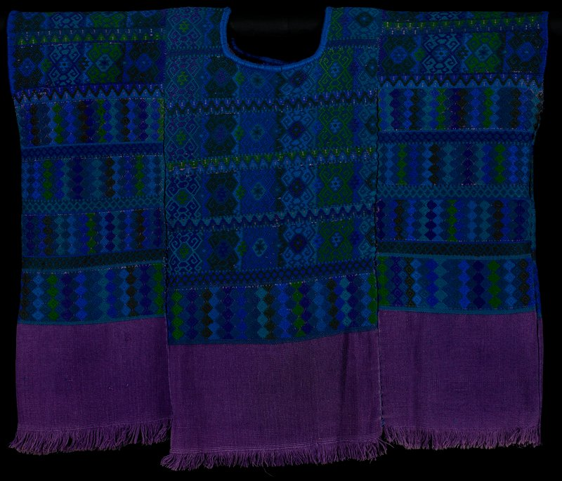 purple body with frayed hem; geometric designs in blues, purples and greens; rounded neckline trimmed in blue