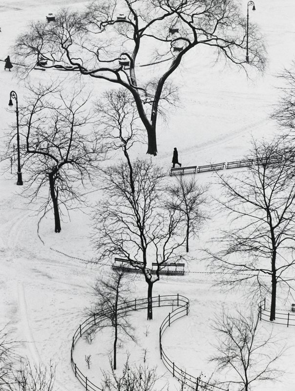 bare trees, lamp poles, benches and fences around curving pathways in the snow; dark figure at center - another in upper left corner