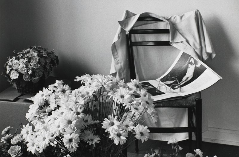 bouquets of flowers on floor and on box at left; chair at right with a shirt hanging on its back and a book and eyeglasses on its seat