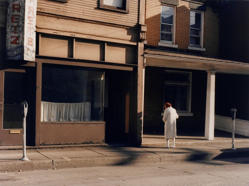 old woman seen from back, wearing white coat, socks and shoes, and a red plaid headscarf, on a deserted street with empty storefront at left; two parking meters; old sign, upper left corner