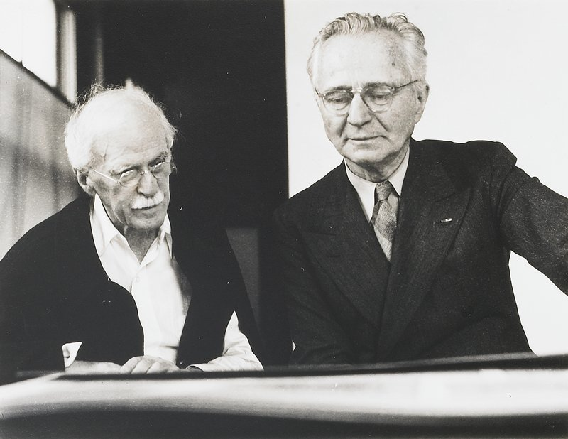 Steichen and Stieglitz side by side looking down at something on a table or desk