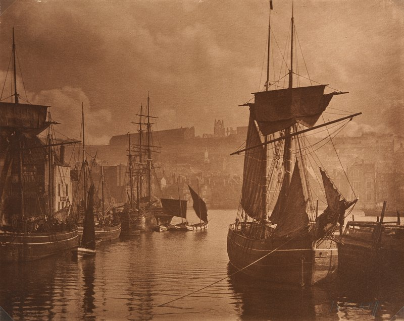 sailing boats at a dock at right and on shore at left in a city, with buildings in background; sepia toned, mottled brown on back of sheet