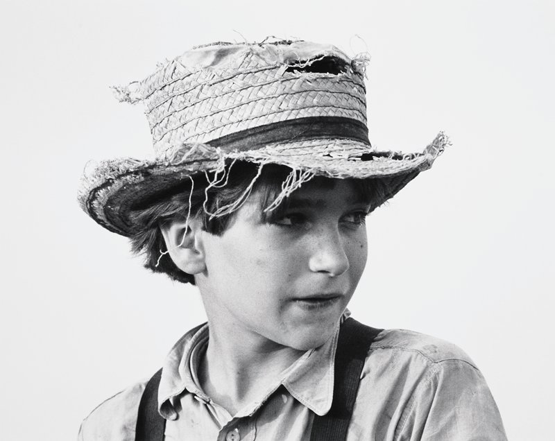 head and shoulders portrait of young boy wearing ragged straw hat