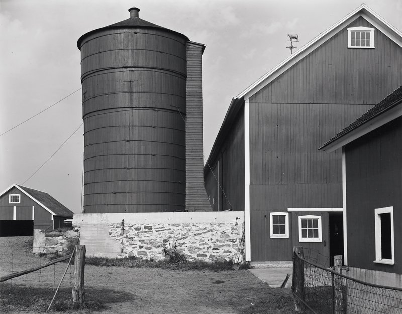 barn with white trim, silo above stone wall; weathervane with cow on top of barn