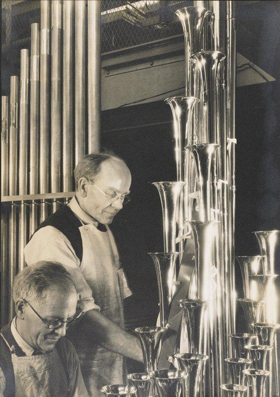 two men assembling pipe organ pipes