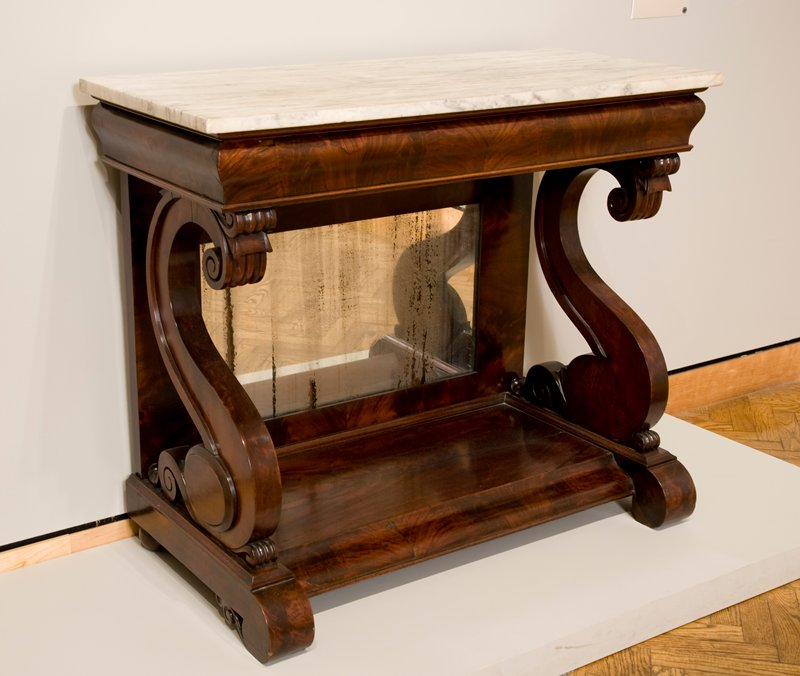 removable veined marble top; open front; heavy scroll on each side, supporting top; mirror on back, bottom; solid flat base; medium finish