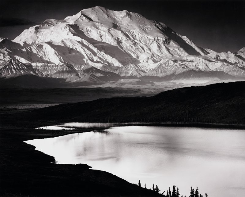 snow-covered mountain with lake in foreground