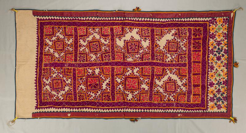 one short end is plain muslin; several multi-colored tassels at edges; small round mirrors in orange and purple blocks of geometric design