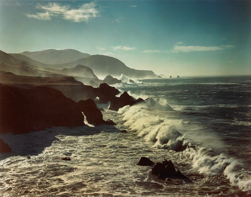 surf breaking on rocks, foreground; headlands on left middle ground