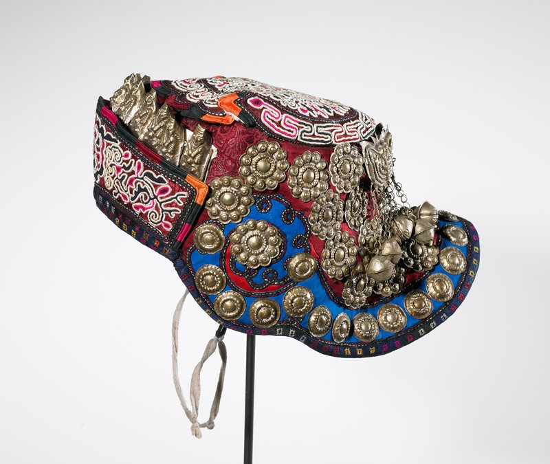 cap with brim on back; predominately maroon and blue fabric with appliqués in floral designs with bees on crown; metal floriform elements, butterflies, bells and fish suspended by chains on back; eleven small metal Buddhas on front; chin strap