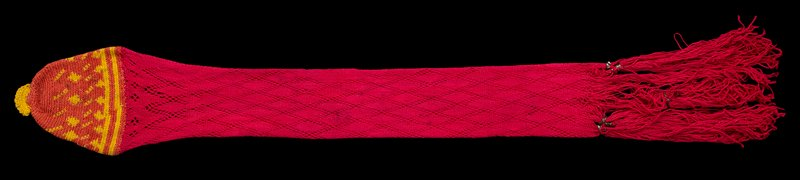 long knitted hot pink tube, with diamond openwork design and tassels with metal (?) accents; bottom is rounded with orange and yellow tightly-knitted piece