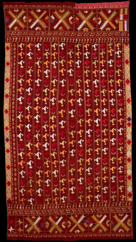 13 rows of multicolored birds (predominately orange, pale green, white and magenta) embroidered on rust-colored fabric; wide X-motif end bands; various geometric border designs embroidered in multicolors; pink end strip at one corner