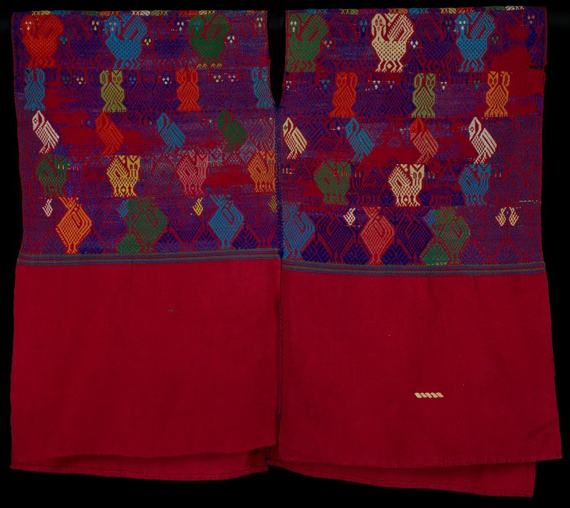 two panels sewn together to create pullover poncho with open sides; red; woven in multicolors (primarily purple) with birds, owls, quadrupeds, deer and human figures; small line of yellow stitching in one area near hem; two small green stitches on opposite panel on same side
