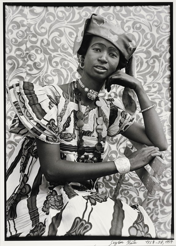 African woman seated on a bench wearing turban-like head cloth, large print dress, several necklaces; bracelet carved with oval motif