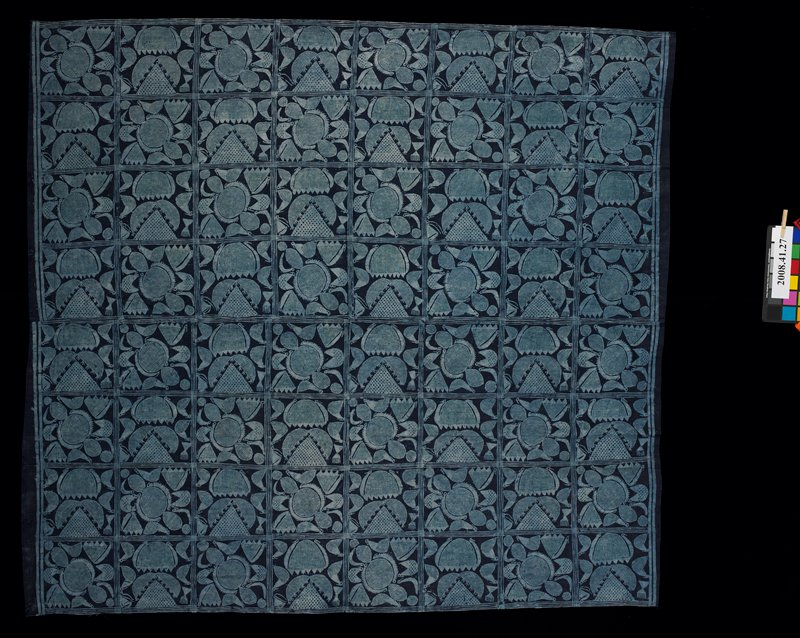 two panels sewn together and hemmed on two sides; indigo with light blue repeating block designs in two motifs with bird and flower forms, with crosshatching; starch resist