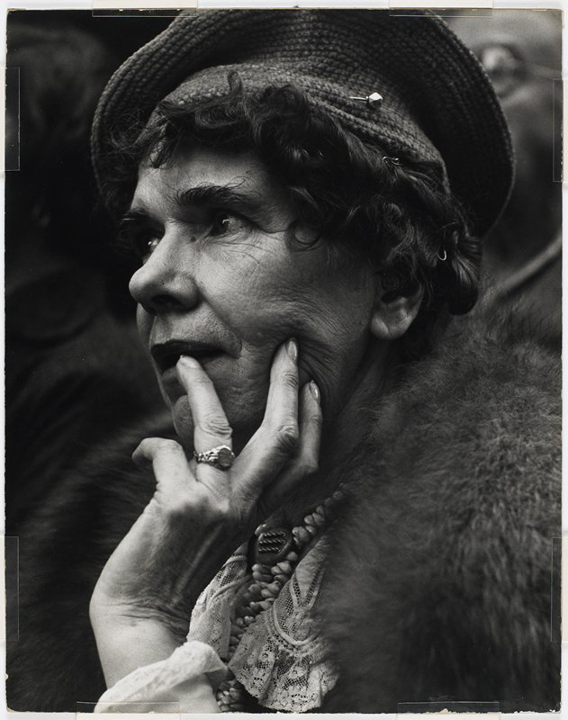 portrait of an elderly woman with short curly dark hair, wearing a knitted cap with a hat pin, beaded necklace, ring, lace collar and fur coat or wrap; mounted on a board