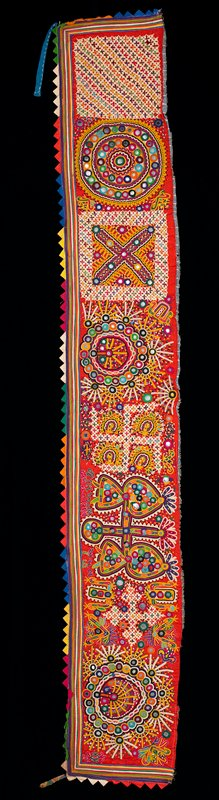 red with triangle trim in bright multicolored fabrics on three sides; appliqué line trim in bright colors on three sides; embroidered overall in bright colors with organic designs, and cross and circle motifs, embellished with mirrors; backed with blue printed fabric