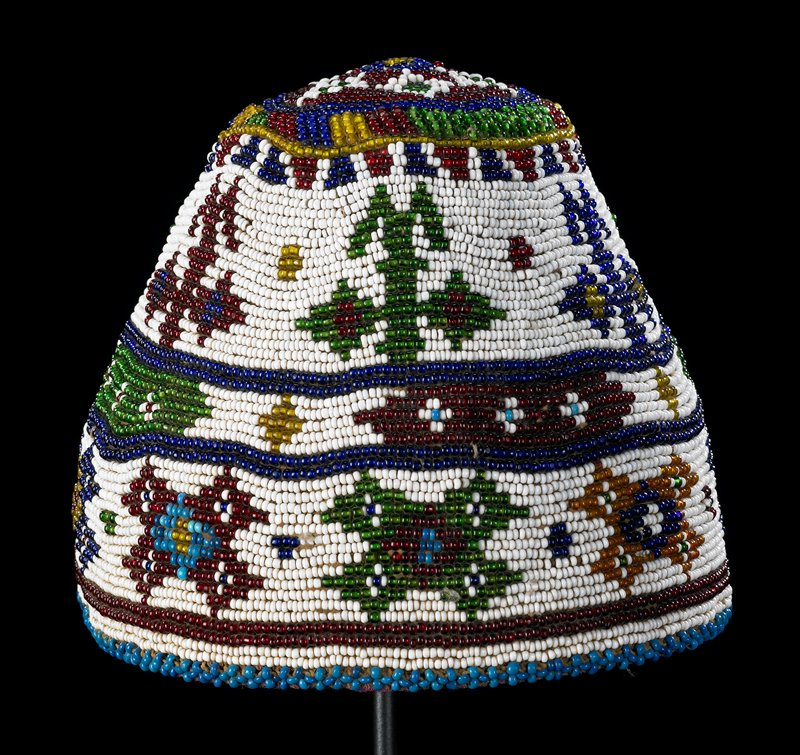 very hard cap/beanie with slightly rounded top; beaded overall in maroon, green, dark blue, light blue, white, orange and yellow beads; star pattern on crown; three bands with geometric tree-like shapes and X's; lined in pink, off-white and pastel printed fabric