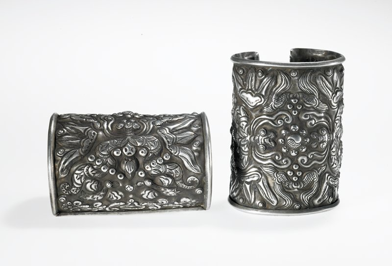 cuff style bracelet with central floral medallion surrounded by bird and feather designs; cloud-like motifs at ends of cuff; all designs are raised