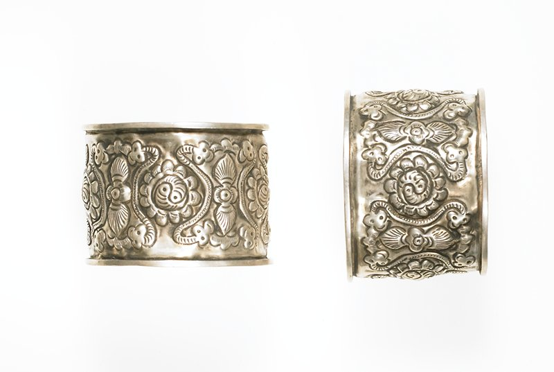 cuff style bracelet; relief motifs include double fish, 2headed snakes, and insects (?); raised bands at top, bottom and ends