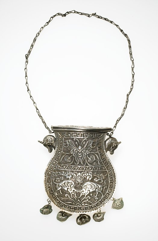 pendant in the shape of a bag; hinged lid; motifs on body include two bulls fighting with a butterfly above-- elephant head-like motifs with attached spiral rings; five pendant motifs attached at bottom; key design around edges and across middle of bag; scalloped design along outer edges; both sides identical; lid with double fish and phoenix motif