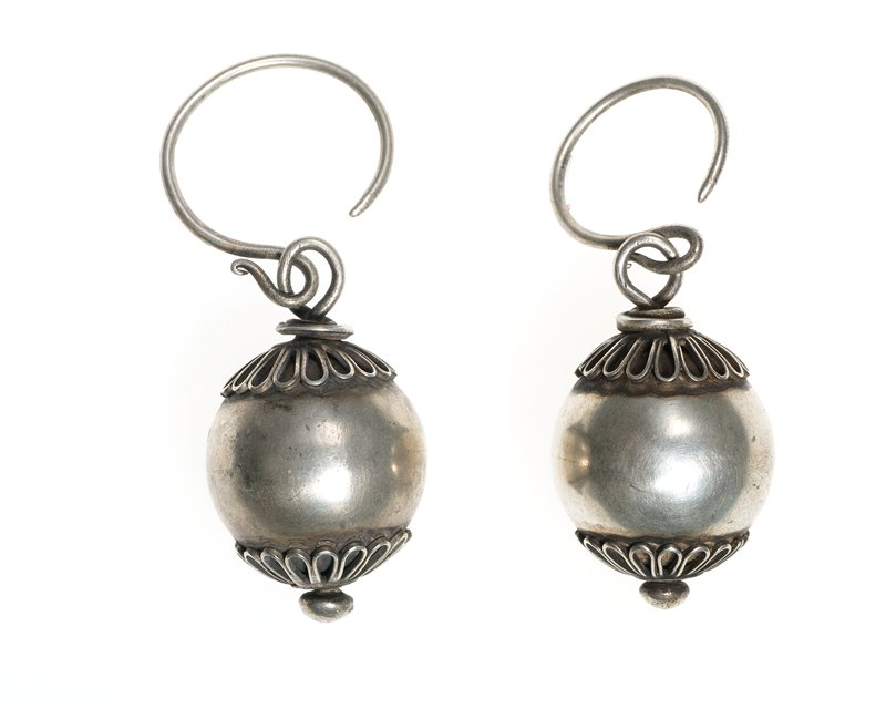 earring made from circle of wire; circle of wire has a sphere hanging from it; top and bottom of sphere are decorated with thin wire and one smaller sphere on the bottom