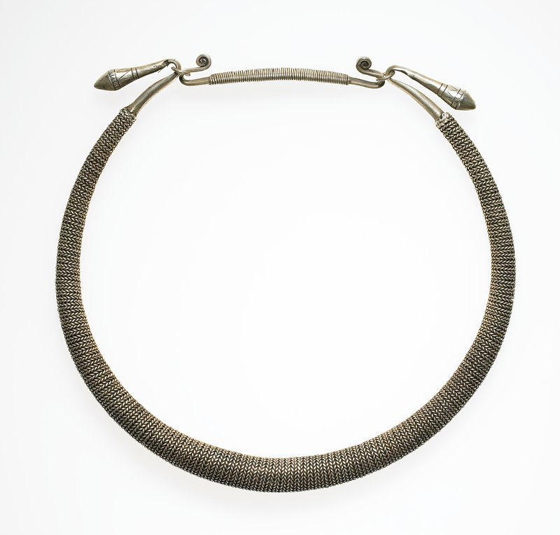 torque with one ring; ring of solid silver covered in tiny, twisted silver wire; looks like it has been braided, but is actually just twisted; ring ends in large cones on each end; connecting piece is solid silver with wrapped small wire
