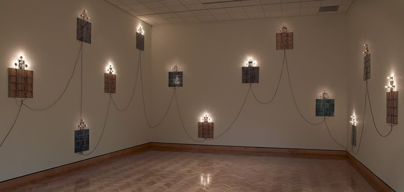 """each unit consists of a vertical framed photographic portrait of a child at top center and four rows of three framed horizontal TV snow-like photographic images in tan, grey, or blue, and a set of three bulb sockets above, each socket with one light bulb, with exposed hanging electrical wiring connecting the units together; any number of units can be installed in any configuration, with the maximum number of 22 units available for installation  The framed portions of the units consist of:  - 22 portraits of children in tin frames, glazed with glass (3 portraits were framed in-house and did not come with borders; an original unframed grey """"snow"""" photo was color photocopied, and the copies were cut into strips to create borders for these portraits per the instructions of curator Patrick Noon--these are labeled on the back of the frames)  - 264 total """"snow"""" photographs in tin frames, glazed with glass:  - 108 tan  - 84 blue  - 72 grey  Additionally there are:  - 3 empty tin frames without glazing (one has an unwelded corner) (ROS, Cab. 6, 4/14/09)  - 3 photographic portraits of children in glassine envelope (ROS, Cab. 6, 4/14/09)  Consumable components not inventoried include:  - 5-watt flat top silver base bulbs (ROS, Cab. 6, 4/14/09) - 5-watt rounded silver base bulbs (ROS, Cab. 6, 4/14/09) - 7-watt rounded silver base bulb (ROS, Cab. 6, 4/14/09) - 15-watt flat top silver base bulbs (ROS, Cab. 6, 4/14/09) - 15-watt rounded elongated gold base bulbs (ROS, Cab. 6, 4/14/09) - 15-watt rounded squat silver base bulbs (ROS, Cab. 6, 4/14/09) - baggie containing European electrical plug and 8-hole electrical junctions (most stamped, """"ML-150 S Sato Parts"""") (ROS, Cab. 6, 4/14/09) - box of brass light bulb sockets (ROS, Cab. 6, 4/14/09) - partial spool on 18/2 gauge black electrical wire (ROS, Cab. 6, 4/14/09)"""