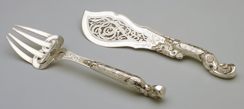 ornate handles; pierced scrolls at bottom of tongs
