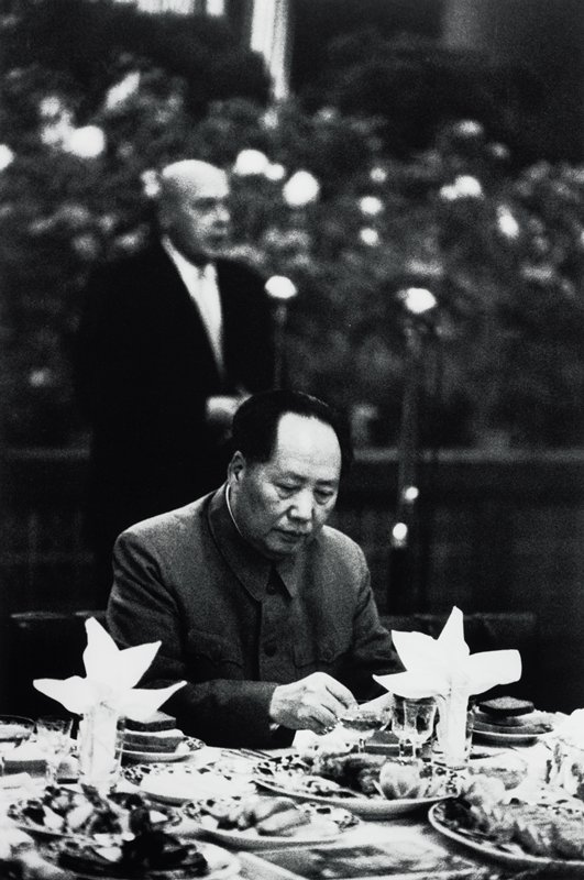 Mao Tse Tung at a table with plates of food; blurry standing man in background
