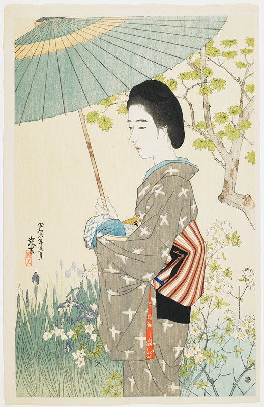 young woman in a grey kimono with white crosses, holding a blue umbrella, standing in front of irises and azaleas in bloom