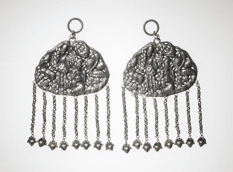 cloud shape oval pendant; motifs include 2 human faces, bird, deer, insects, flowers and foliage; eight small acorn shaped pendants attached by chains; at top one large wire-like loop attached by 3 smaller loops to pendant